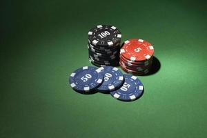 Fichas de casino apiladas sobre fondo verde foto
