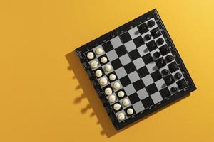 Vista superior del tablero de ajedrez con piezas sobre fondo amarillo foto