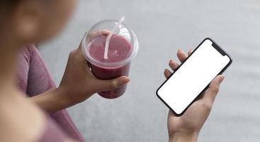 mujer fitness sosteniendo un teléfono inteligente con pantalla en blanco foto
