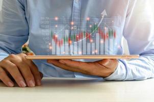 tecnología y finanzas empresariales. concepto de inversión. invertir en bolsa y fondos. hombre de negocios analiza datos financieros, gráficos y operaciones de cambio en una tableta. foto