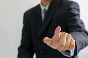 Businessman wearing a suit pointing fingers in front. photo