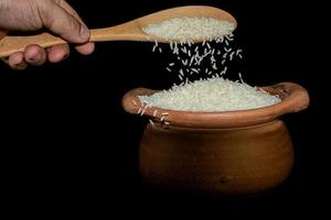 Scoop rice by using a ladle in a clay pot photo