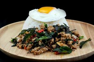 Rice topped spicy fried pork with basil leaves topping, fried eggs on a wooden dish, Pad Krapow Moo is traditional Thai food photo