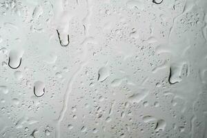 Gotas de lluvia de agua sobre el cristal de la ventana de un coche foto