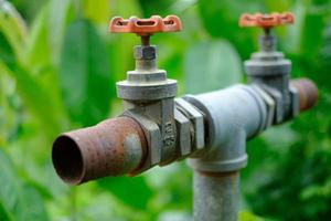 Válvula de compuerta en la tubería en los sistemas de riego controlan el agua para cerrar el lugar antiguo con un fondo borroso foto