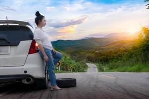 Young beautiful lady standing near car for calling for help on the public road photo