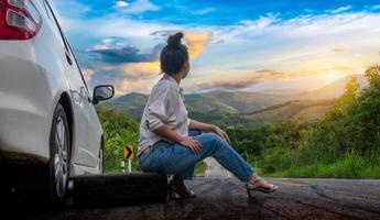 Young beautiful lady sitting near a car for calling for help on the public road in a forest area with a mountain and sky background photo