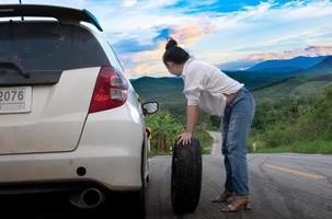 Young attractive woman in formal wear holding a spare car tire on the public road in a forest area with a mountain and sky background photo