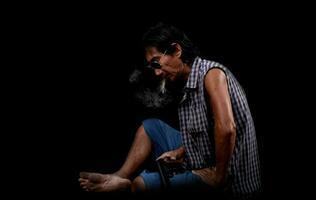 Retrato delgado anciano asiático fumando y sosteniendo una pistola sobre un fondo negro foto