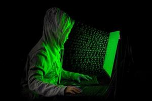 Women hacker breaks into government data servers and infects their system with a virus at his hideout place, dark blue atmosphere, hooded lady using laptop with binary code background, malware concept photo