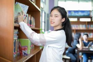 estudiante femenina encontrando libros de la biblioteca foto
