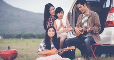 Family playing ukulele together on camping trip photo