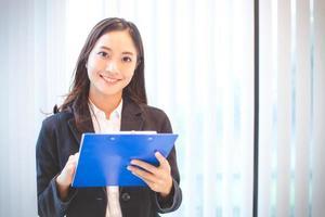 mujer sonriendo y sosteniendo el tablero de clip foto