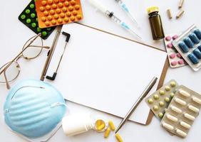 Portapapeles azul máscara médica y pastillas de medicina foto