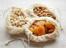 Eco bags with pistachios almonds and dried apricots photo
