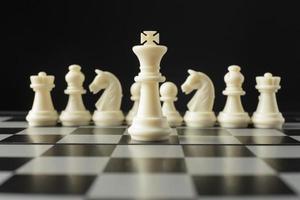 Piezas de ajedrez blancas en concepto de rey de tablero de ajedrez foto