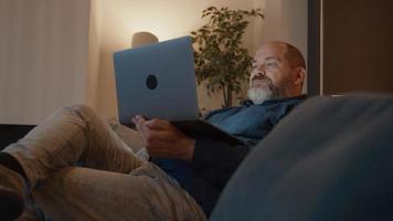 El hombre tiene una llamada en línea en el portátil en el sofá video