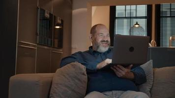 El hombre tiene una llamada en línea en el portátil en el sofá sonriendo video