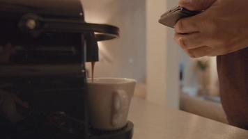 La mano del hombre que sostiene el teléfono inteligente y el café se queda sin máquina video