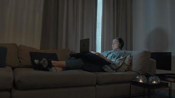 Mujer acostada en el sofá con auriculares y portátil video