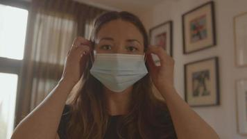 Mujer poniéndose mascarilla mirando a la lente video