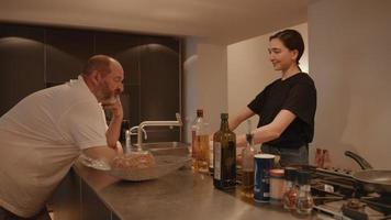 Mujer preparando comida mientras habla con el hombre en la cocina video