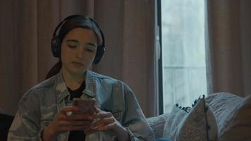 Mujer en el sofá con auriculares escribiendo en el teléfono inteligente video