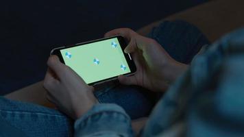 manos de mujer sosteniendo smartphone con pantalla verde video