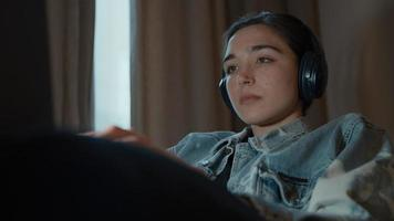 mujer, en, sofá, con, auriculares, mirar, computadora portátil video
