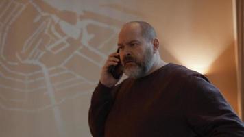 hombre en la sala hablando por teléfono celular video