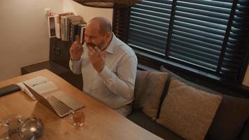 El hombre en la mesa se enoja mientras tiene una llamada en línea video