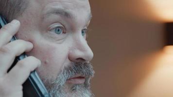 Hombre mirando por la ventana mientras habla por teléfono inteligente video