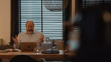 El hombre en la mesa con una llamada en línea en un portátil gesticulando video