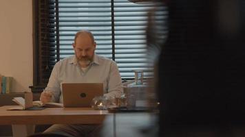 hombre en la mesa mirando portátil y libro video