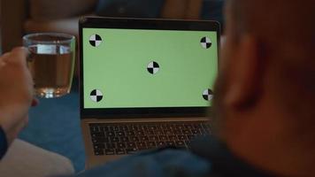 Hombre hablando con un portátil de pantalla verde sosteniendo una taza de té video