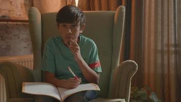 niño en sillón hablando y escribiendo en el libro de ejercicios video