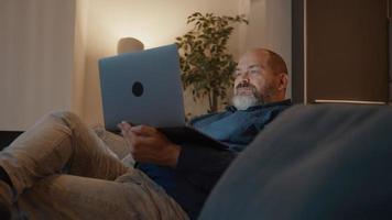 hombre mirando portátil sentado en el sofá video