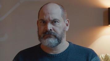 hombre mirando enojado en la lente de la cámara video
