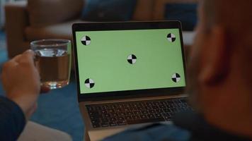 Hombre mirando portátil con pantalla verde bebiendo té video