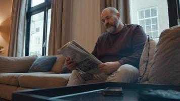 Hombre leyendo el periódico en el sofá contesta el teléfono video