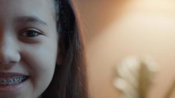 la mitad derecha de la cara de las niñas sonriendo a la lente de la cámara video