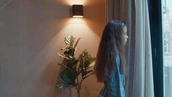 niña de pie mirando por la ventana video