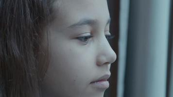 niña mirando por la ventana video