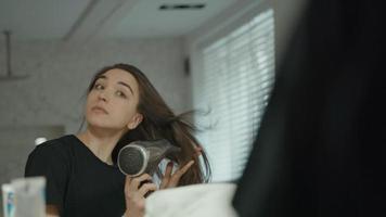 Femme à l'aide d'un sèche-cheveux dans la salle de bains à la recherche de miroir video
