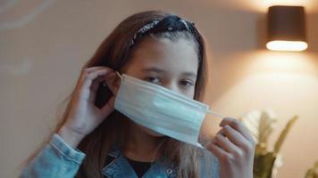 Chica poniéndose mascarilla mirando a la lente de la cámara video