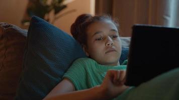 niña acostada en el sofá con tableta video