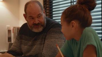 hombre hablando con niña haciendo sus deberes en la mesa video