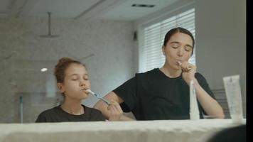 kvinna och flicka borsta tänderna i badrummet video