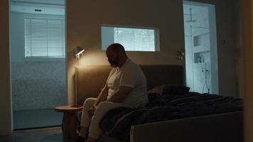 hombre sentado en el borde de la cama con aspecto cansado video