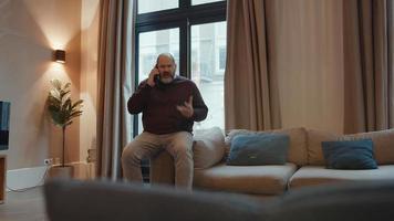 Hombre en la sala de estar enojado mientras habla por teléfono inteligente video